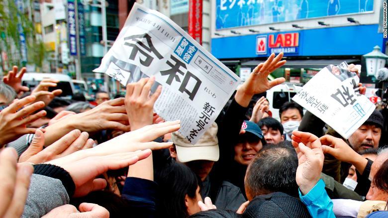 일본의 새 연호 '레이와'가 발표된 신문 호외를 서로 집으려고 사람들이 아우성치는 장면