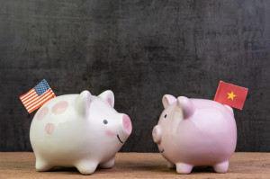US and China trade war or tariffs negotiation concept, piggy bank with United state national flag face to face with one with China flag on wood table dark background with copy space