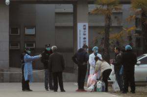 28일(현지시간) 중국 베이징역에서 승무원이 베이징 도착 승객 전원 대상으로 체온을 재고 있다. [연합=헤럴드경제]