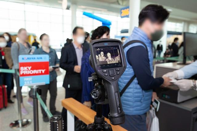 28일 인천공항 대한항공 탑승 카운터에서 탑승객들이 열화상 카메라로 발열검사를 받고 있다.  (사진=대한항공 제공)