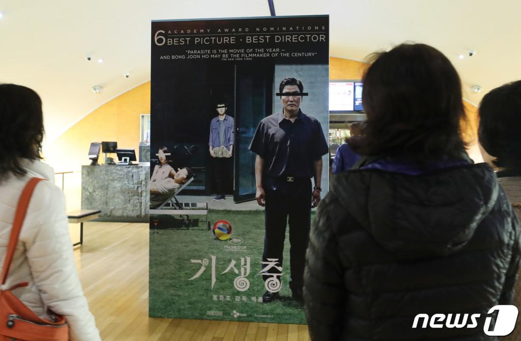 10일(현지시간) 미국 CGV 로스앤젤레스점에서 아카데미 4관왕에 빛나는 봉준호 감독의 영화 '기생충'이 상영되고 있는 가운데 관객들이 포스터를 바라보고 있다.[뉴스 1]