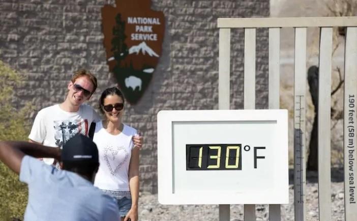 데스밸리 퍼네이스 크릭 방문객센터의 온도표시판이 16일 화씨 130도를 나타낸 가운데 한 커플이 기념사진을 찍고 있다.